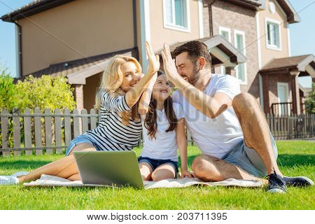 Best team. Lovable young family sitting on the grass in their backyard and giving each other a high five
