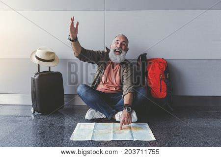 Hilarious mature bearded tourist is pointing on certain place at map looking ahead with happy laugh. He sitting near wall in waiting-hall. Portrait. Copy space on right side