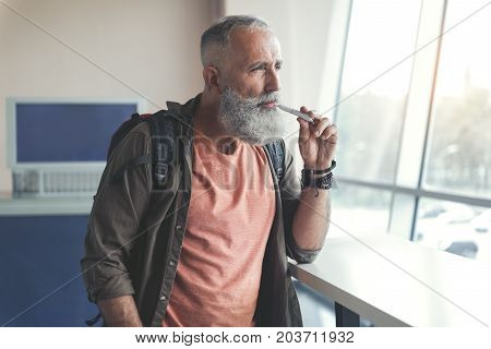 Thoughtful bearded elder man is smoking electronic cigarette and looking at window with sadness. He waiting for his trip. Waist up portrait. Copy space on left side