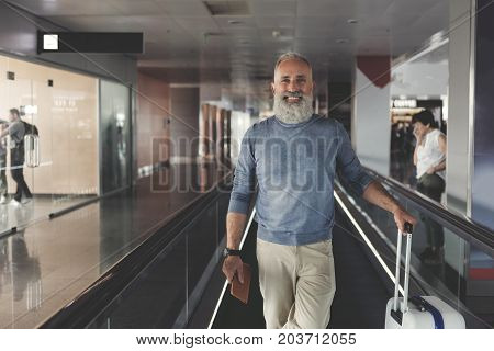 Happy bearded mature tourist is standing on moving tape and looking at camera with bright smile. Waist up portrait. Copy space on left side
