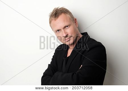 Smiling young man in black clothes standing against white background Concept of self confident man. Positive man emotion