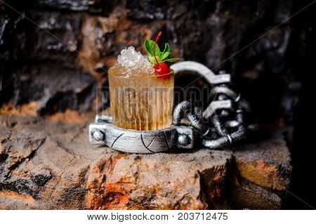 Alcohol cocktail with crushed ice red cherry and mint on the wall background