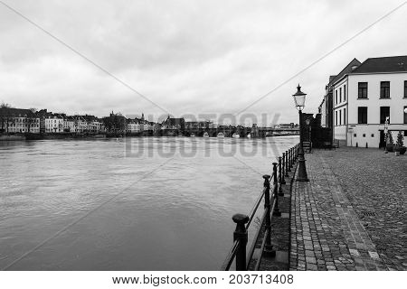 MAASTRICHT NETHERLANDS - JANUARY 09 2015: View of Maastricht city centre with its partly medieval bridge on the Meuse river. Black and white. Maastricht is the oldest city of the Netherlands and the capital city of the province of Limburg.
