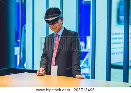 Vladivostok, Russia - September 7, 2017: Young Man Wearing Virtual Reality Headset Or Goggles Lookin
