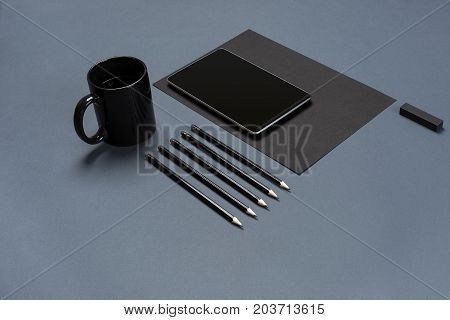 Flat lay of blank black paper sheet, black stationery items and coffee cup on gray desktop. Mock up. Concept of creative work space