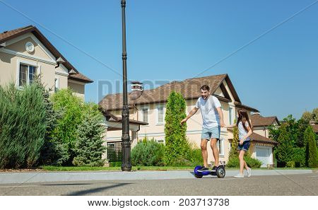 By your side. Adorable little girl holding her fathers hand and following him while he riding a self-balancing scooter down the street