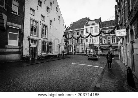 MAASTRICHT NETHERLANDS - JANUARY 09 2015: Old narrow street in the historic center. Black and white. Vignetting. Maastricht is the oldest city of the Netherlands and the capital city of the province of Limburg.