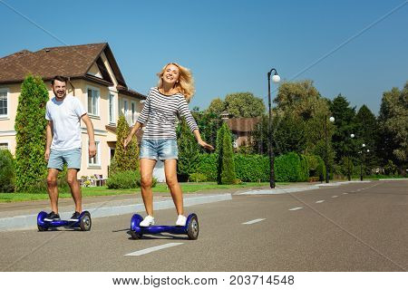 Enjoying the ride. Lovely young couple riding self-balancing scooters down their neighborhood and having fun