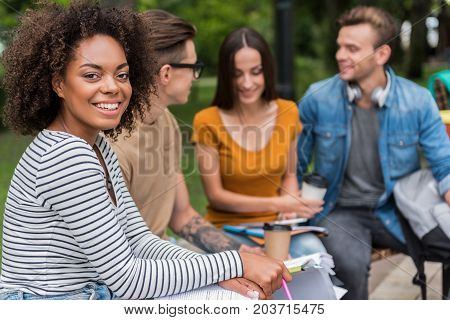 I like spending time with my friends. Portrait of happy mulatto girl looking at camera and smiling. Men and woman are sitting and chatting on background