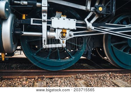 Old vintage train wheel with green metal spoke parked on rusty train track