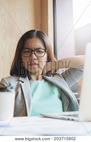 Asian Business woman having pain on her shoulder and neck while her working.