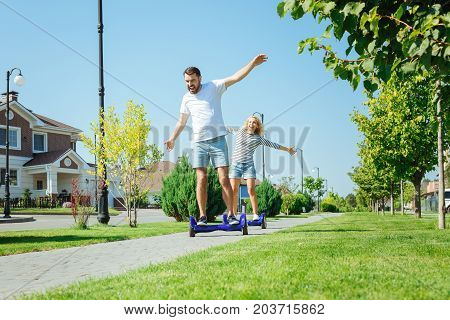 Sweet freedom. Joyful pleasant man and woman riding self-balancing scooters, following each other and laughing while spreading the hands