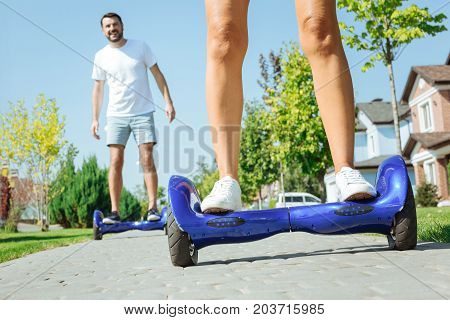 Testing new device. The focus being on the bare legs of a female standing on a blue hoverboard while her husband following her on the same hoverboard