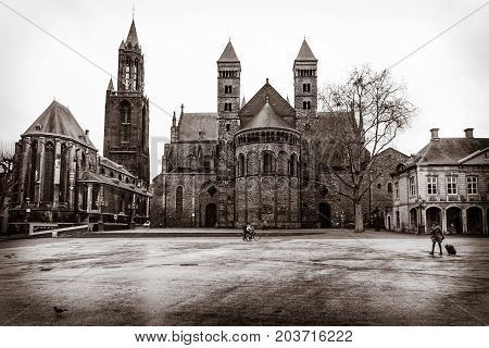 MAASTRICHT NETHERLANDS - JANUARY 09 2015: Vrijthof square. Evangelical Church of John the Baptist (left) and the Basilica of Saint Servatius (right). Vintage toning. Sepia.