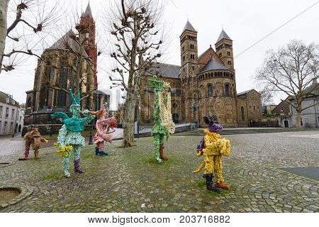 MAASTRICHT NETHERLANDS - JANUARY 09 2015: Vrijthof square. People and animals in stone and bronze ('t Zaat Herremenieke) by Han van Wetering. Sculpture dedicated to the carnival. In the background Evangelical Church of St. John and Basilica of St. Servati