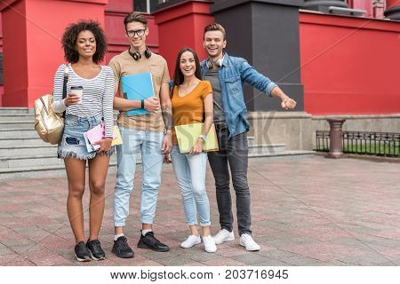 Enjoying education together. Full length portrait of happy students standing near university building and laughing. They are looking at camera with joy. Copy space