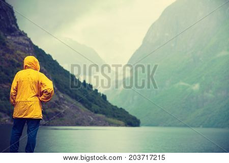 Tourism vacation and travel. Male tourist looking at mountains and fjord Sognefjord in Norway Scandinavia. Misty foggy day rainy weather