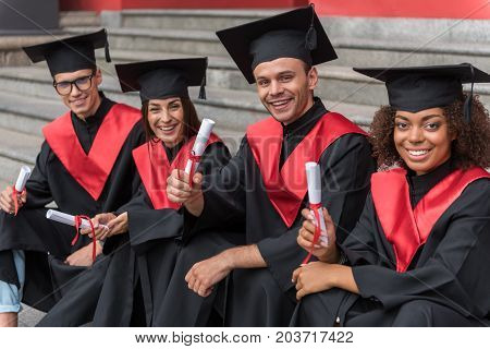 Finally we got a diploma. Portrait of happy graduates showing certificate of high education and smiling. They are looking at camera with excitement