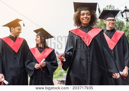 Low angle portrait of happy young graduates walking outdoors and carrying their diploma papers. Pretty mulatto girl is looking forward with aspiration and smiling. Bright future concept