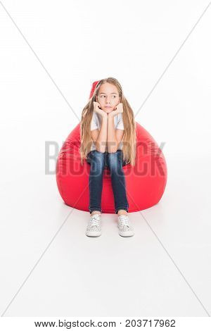 sad female youngster sitting in red bean bag chair isolated on white