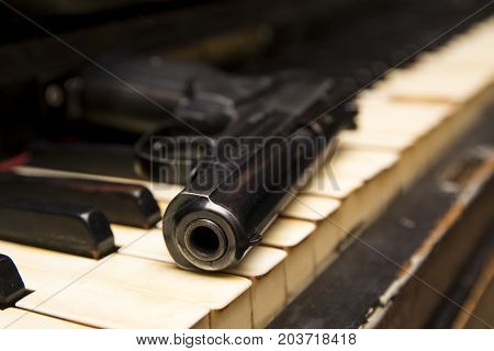 Dlack Gun On The Keys Of Piano Close Up