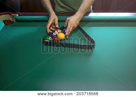 Referee preparing the billiard balls on green pool table