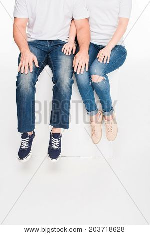 cropped view of couple sitting together on white cube isolated on white