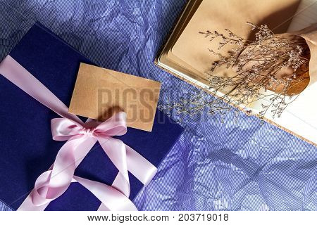 The Dark blue gift box with ribbon decoration with book and flower on polka blue paper Happy Father's Day or celebration gift concept top view and overhead shot