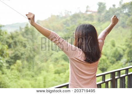 Rear view. Happy Relaxed Asian woman waking up and Outstretched her arms on green natural background at balcony in the morning. Resting on Holiday.