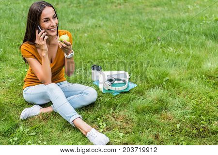 Glad caucasian girl is enjoying communication by smartphone and smiling. She is relaxing on green grass near various learning material. Student is holding fruit