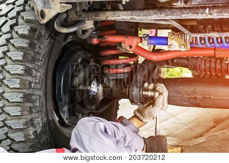 Car mechanic in grey uniform using a wrench to tighten the nut under the car for maintenance Automotive industry and garage concepts.