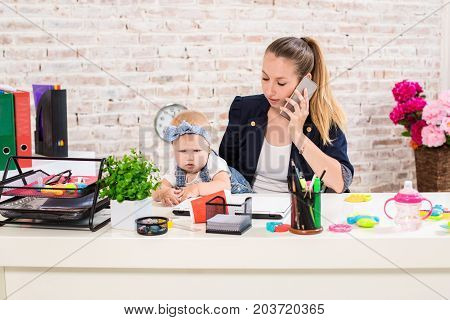 Family Business - telecommute Businesswoman and mother with kid is making a phone call. At the workplace, together with a small child