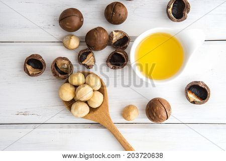The Macadamia Nut Oil and peeled macadamia nut on white table use for Healthy Skin and Hair and Natural Healing Oil Treatment overhead and top view