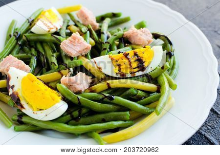 Fresh summer warm salad with cooked green beans tuna boiled eggs and sauce balsamico glassa in white plate on black stone background. Healthy eating concept. Selective focus.