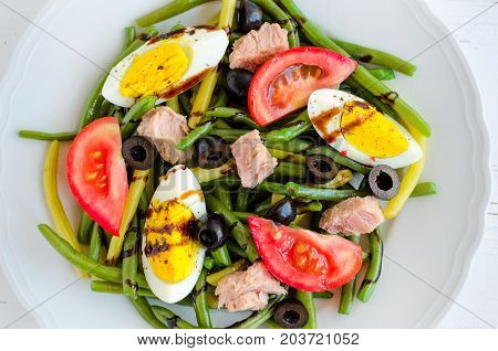 Summer warm salad with cooked green beans tuna tomatoes boiled eggs and sauce balsamico glassa in white plate on wooden background. Healthy eating concept. Top view.