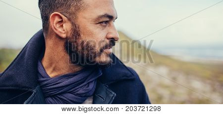 Close up of caucasian man looking away. Portrait of young man with beard standing outdoors.