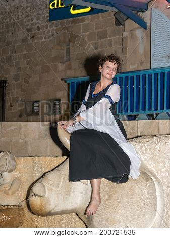 Tel Aviv-Yafo Israel September 08 2017: A girl - a member of the Knights of Jerusalem club dressed in the traditional costume of a medieval lady sits on a bull statue at night in the old town of Yafo in Tel Aviv-Yafo Israel