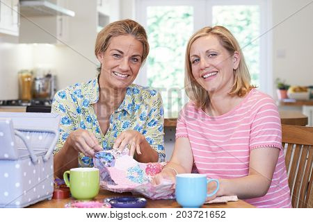 Portrait Of Two Mature Women Sewing Quilt Together