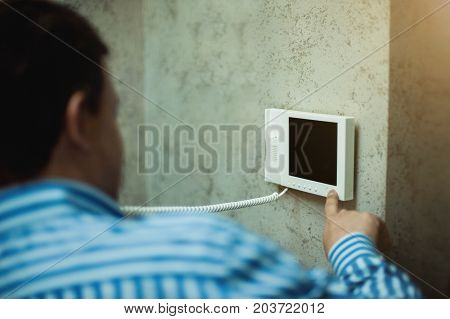 The man with his hand presses the button in the intercom