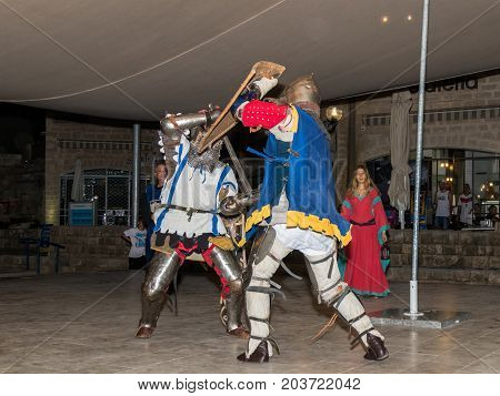 Tel Aviv-Yafo Israel September 08 2017: Members of the Knights of Jerusalem club dressed in the traditional armor of a knight are fighting on swords at night in the old town of Yafo in Tel Aviv-Yafo Israel