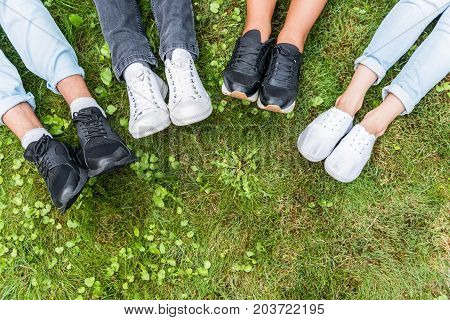 Close up top view of feet with sneakers of young men and women lying on grass. Copy space