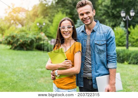 Waist up portrait of happy young students standing and embracing in park. Girl is keeping folder with paper while guy is carrying laptop. They are looking at camera and smiling. Copy space