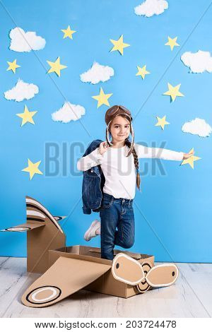 Little dreamer girl playing with a cardboard airplane at the studio with blue sky and white clouds background. Childhood. Fantasy, imagination.