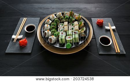 Japanese restaurant, sushi roll platter on black rustic wood background and black slate plates. Set for two with chopsticks, ginger, soy, wasabi.