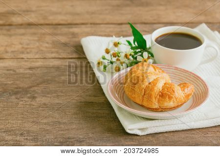 Homemade croissant on plate served with black coffee or americano. Delicious and quick breakfast with fresh croissant and coffee. Croissant and black coffee for breakfast on wood table with copy space. Coffee and croissant for coffee break.