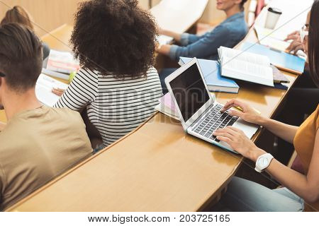 Top view of confident smart female student writing down lecture on her laptop. She is sitting at table near her group mates