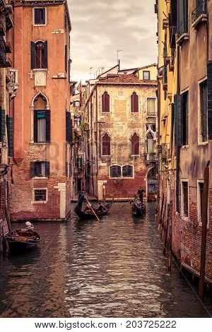 Gondolas with tourists floats along the narrow canal in Venice, Italy. Gondola is the most attractive tourist transport in Venice.