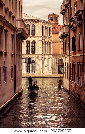 Gondola with tourists floats along the narrow canal in Venice, Italy. Gondola is the most attractive tourist transport in Venice.