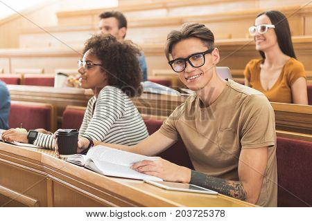 Portrait of smart happy young man reading textbook on seminar. He is looking at camera and smiling