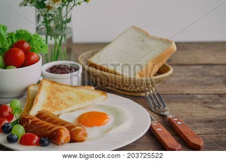 Homemade breakfast with sunny side up fried egg toast sausage fruits vegetable strawberry jam in side view with copy space. Delicious homemade american breakfast concept for background or wallpaper. American breakfast for family.